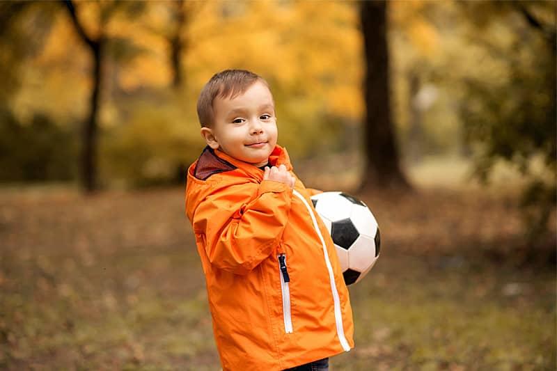Kleiner Junge in oranger Jacke und Fußball im Arm, steht in einem herbstlichen Park