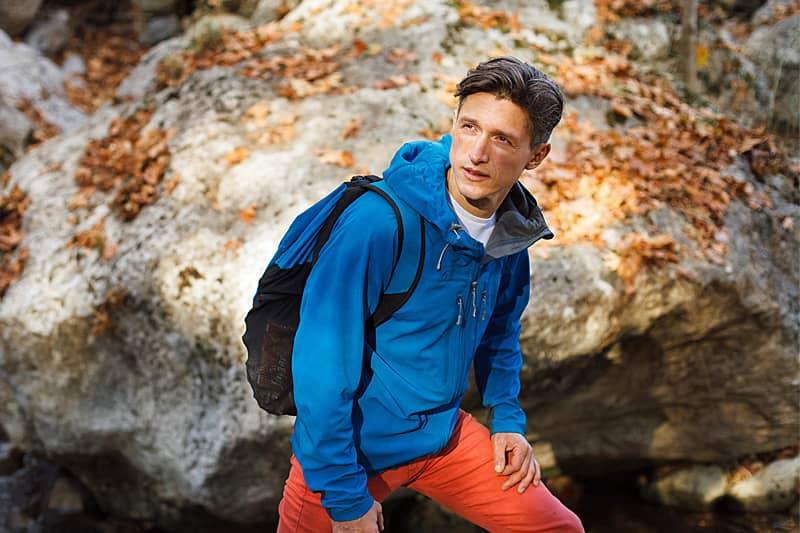 Junger Mann in Outdoor-Bekleidung  wandert durch den Herbstwald