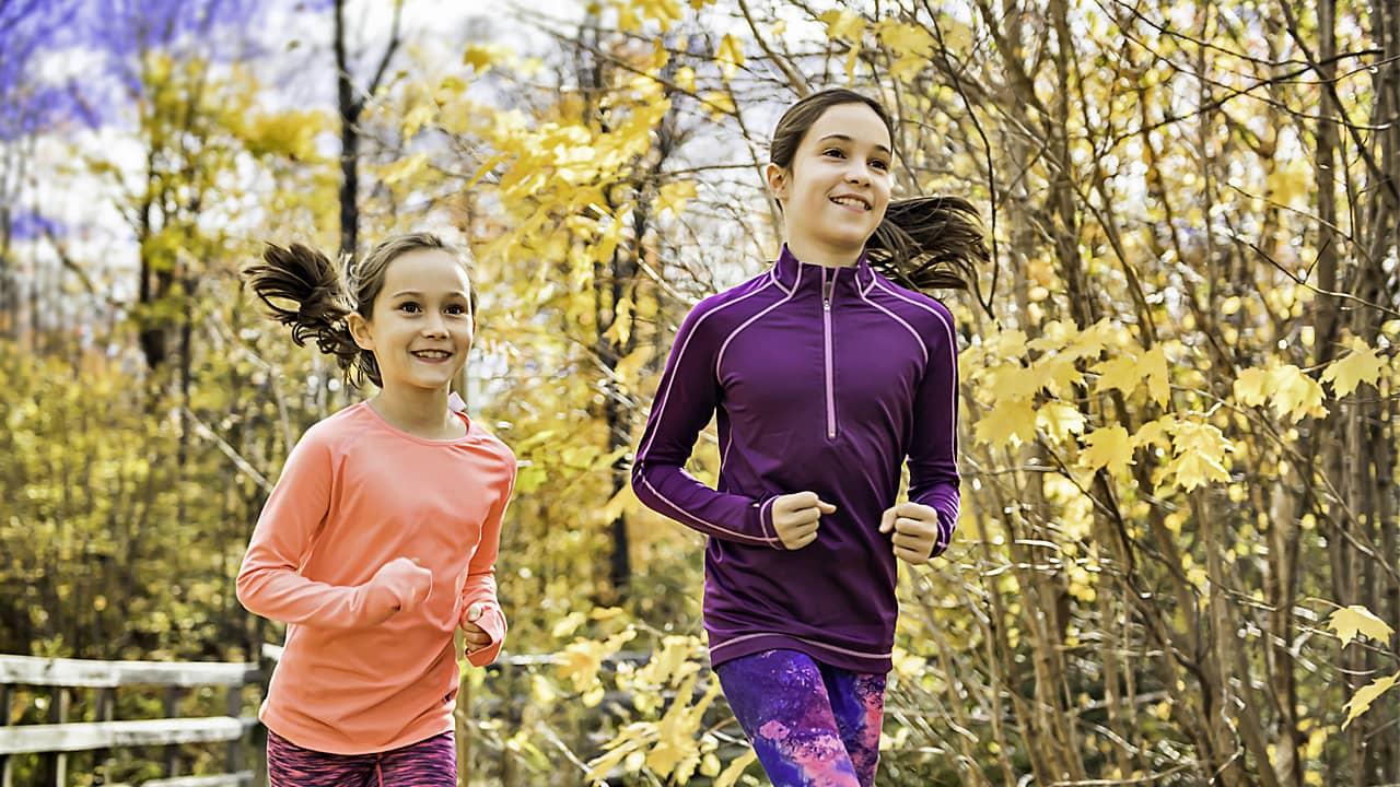 Zwei sprotlich gekleidete  Mädchen laufen durch einen Herbstwald