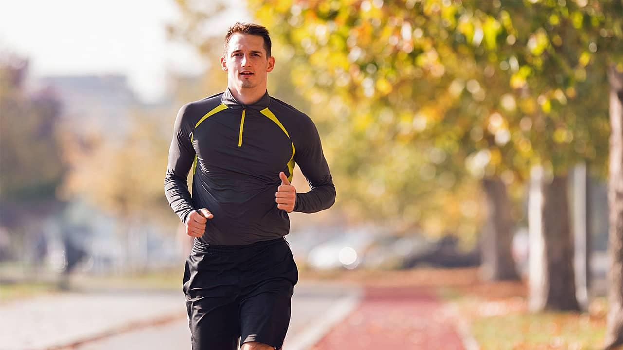 Junger Mann, der Sportkleidung trägt und im Herbst im Park joggt