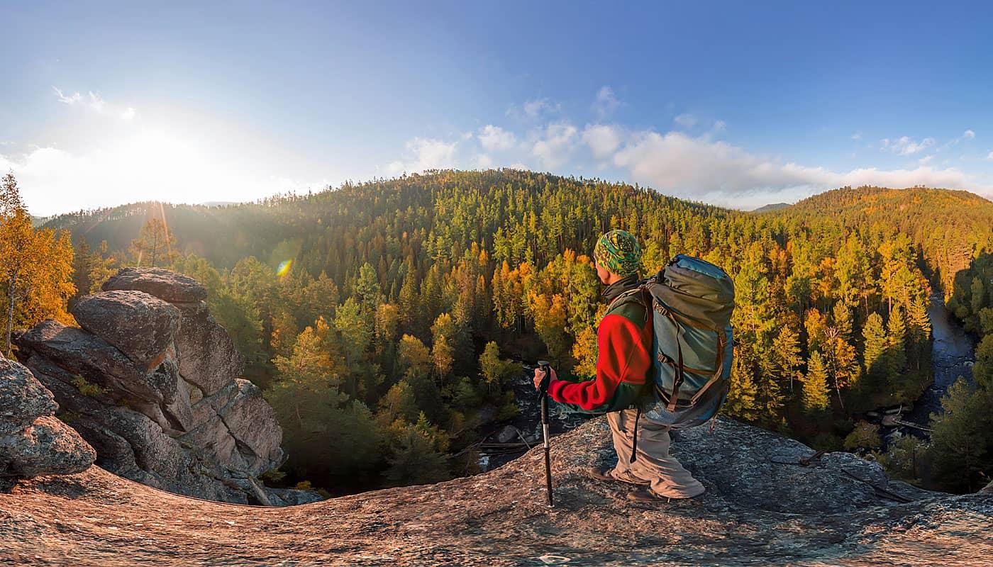 Rucksacktourist auf dem Gipfel eines Felssturzes in der Morgendämmerung. Zylindrisches 360-Grad-Panorama