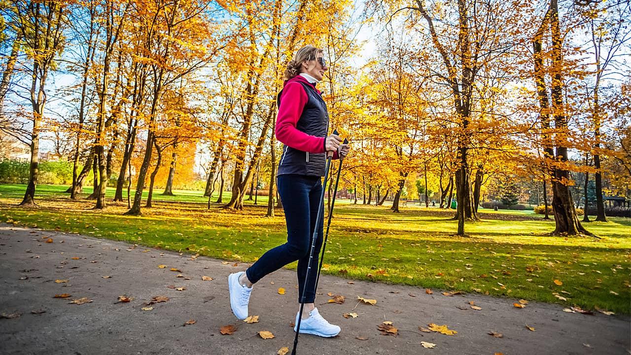 Frau beim Nordic Walking in einem Park