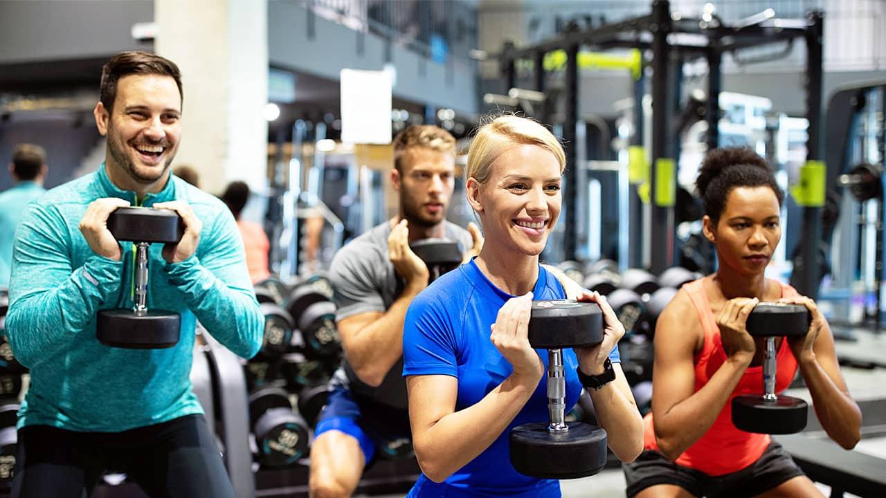 Gruppe von sportlichen Frauen und Männern im Fitnessstudio machen Fitness-Übungen