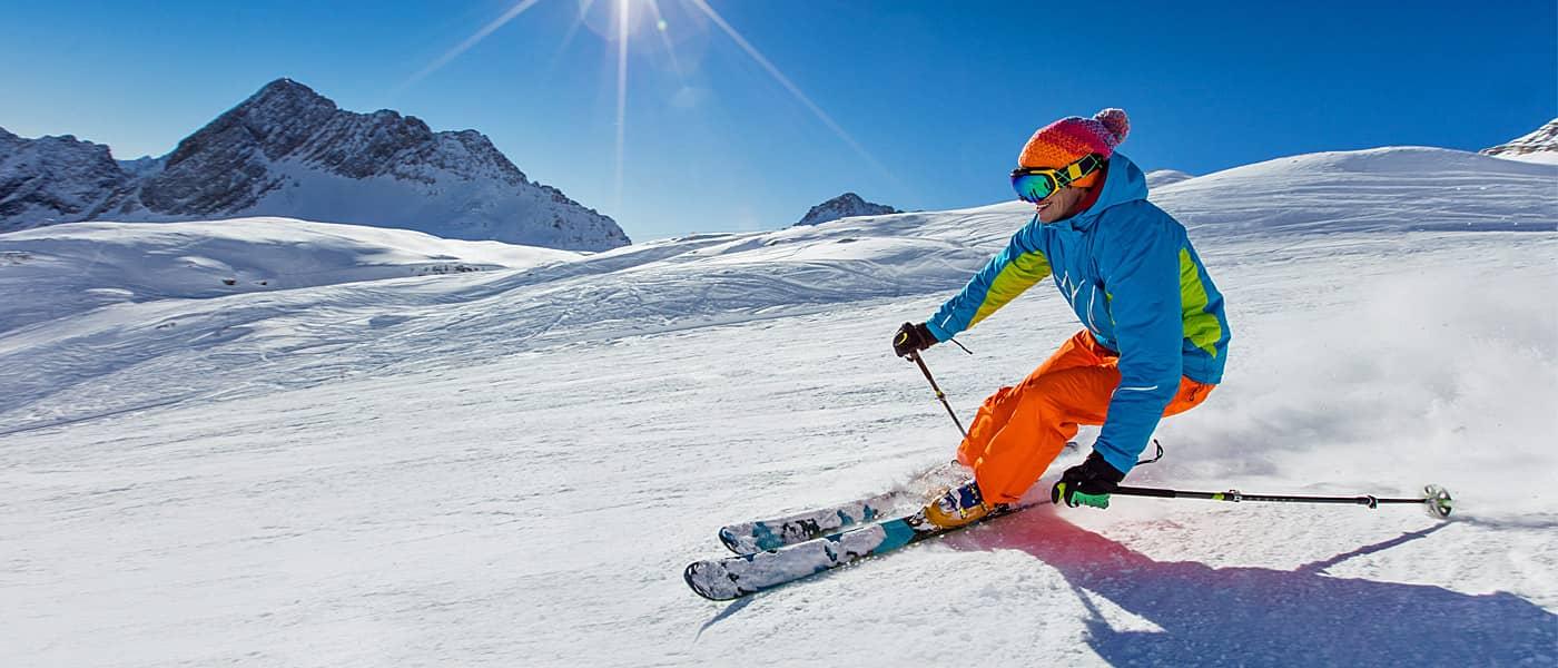 Skifahrer beim Abfahrtslauf im Hochgebirge