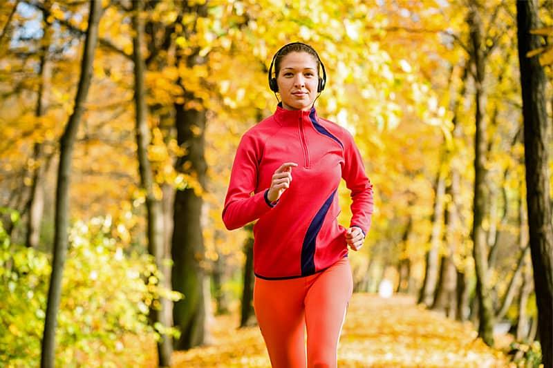 Frau in Sportbekleidung und Kopfhören joggt durch einen herbstlichen Park
